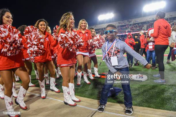A young fan dances as the cheerleaders watch before the football game between the Temple Owls and Houston Cougars on November 10 2018 at TDECU...
