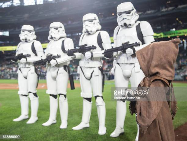 A young fan dressed as a jawa waits to deliver the game ball while standing in front of a row of stormtroopers characters from the the Star Wars film...