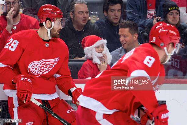 A young fan dressed at Santa Claus next to Brendan Perlini of the Detroit Red Wings during an NHL game against the Arizona Coyotes at Little Caesars...
