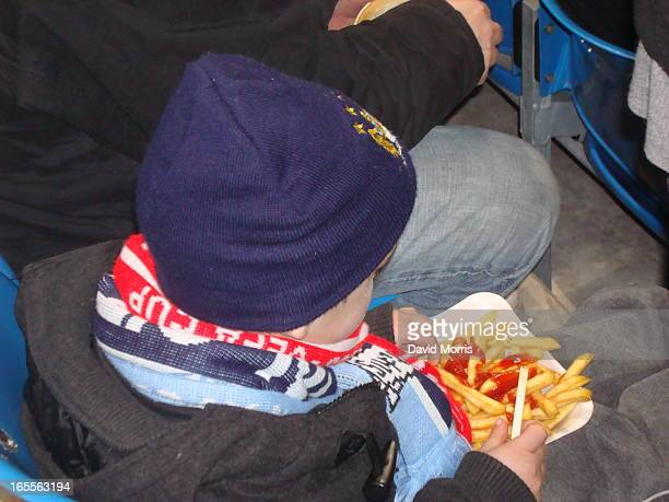 Young fan eating half time chips at Manchester City versus Bolton in the English Premier League at the City of Manchester Stadium, 9th February 2010