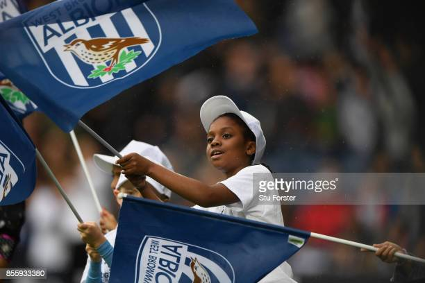A young fan flys a flag during the Premier League match between West Bromwich Albion and Watford at The Hawthorns on September 30 2017 in West...