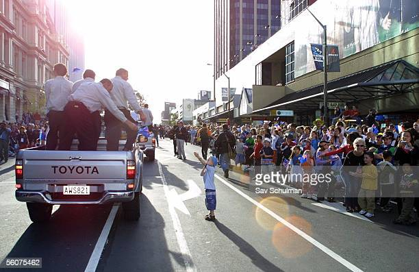 A young fan from the crowd tries to get a closer look at Team NZ as the parade down Queen St during the 2003 America's Cup and Louis Vuitton Cup...