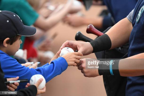 A young fan gets an autograph prior to a spring training game between the Cincinnati Reds and the Seattle Mariners at Peoria Stadium on March 21 2019...