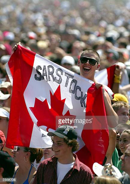 "Young fan holds a Canadian flag with ""SARStock"" printed on it during the SARS relief concert held at Downsview Park July 30, 2003 in Toronto, Canada...."