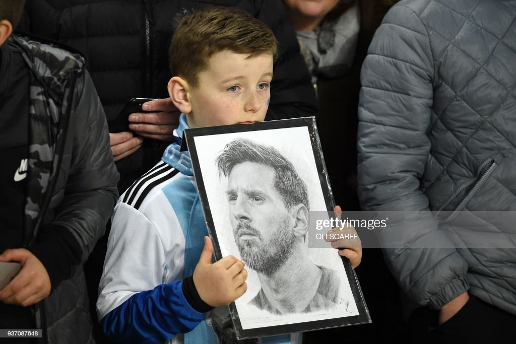 TOPSHOT - A young fan holds a picture of Argentina's striker Lionel Messi in the crowd ahead of the International friendly football match between Argentina and Italy at the Etihad stadium in Manchester, north west England on March 23, 2018. / AFP PHOTO / Oli SCARFF