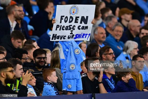 Young fan holds a sign asking for the shirt of Manchester City's English midfielder Phil Foden during the English League Cup third round football...