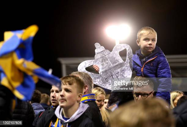 A young fan holds a tin pot FA Cup as Shrewsbury fans celebrate on the pitch during the FA Cup Fourth Round match between Shrewsbury Town and...