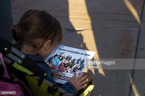 A young fan holds her Blackhawks Ice Crew poster prior to the NHL game between the Buffalo Sabres and the Chicago Blackhawks on October 11 2014 at...