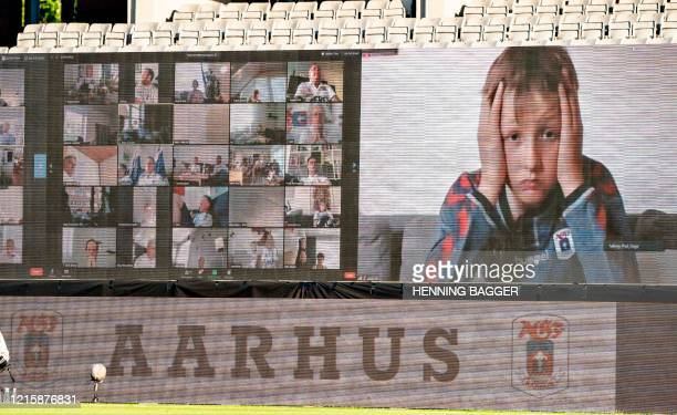 A young fan holds his head as fans are streamed live on to the screens on the sidelines during the 3F Super League football match between AGF and...