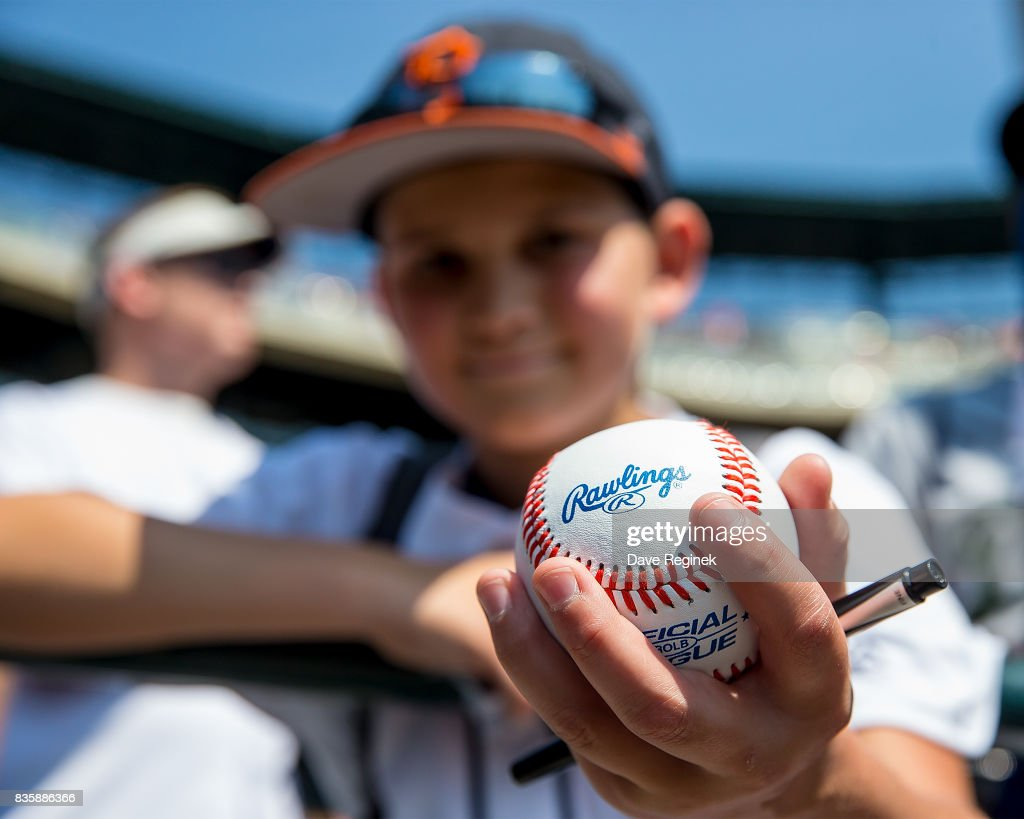 A young fan holds out his baseball in hopes of an autograph before a MLB game between the Detroit Tigers and the Los Angeles Dodgers at Comerica Park on August 20, 2017 in Detroit, Michigan.