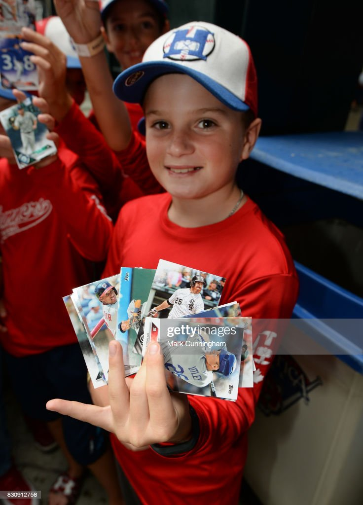 A young fan holds up a group of Topps baseball cards which were given out to fans to celebrate National Baseball Card Day prior to the game between the Detroit Tigers and the Minnesota Twins at Comerica Park on August 12, 2017 in Detroit, Michigan. The Tigers defeated the Twins 12-11.
