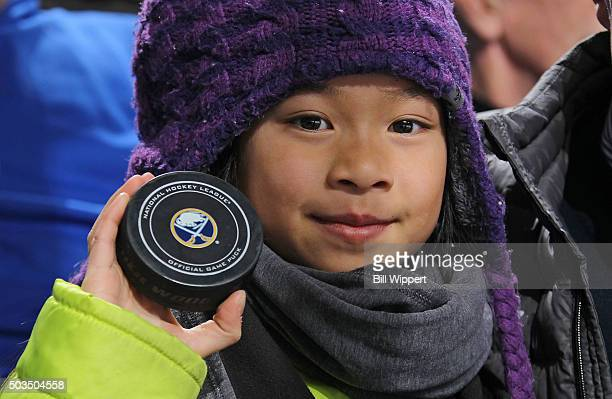 A young fan holds up a puck she received while attending the Buffalo Sabres game against the Florida Panthers during an NHL game on January 5 2016 at...