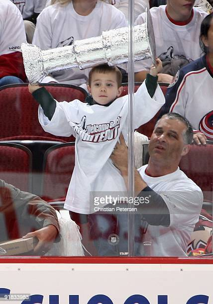 A young fan holds up a stanley cup in the NHL game between the Columbus Blue Jackets and the Phoenix Coyotes at Jobingcom Arena on October 10 2009 in...