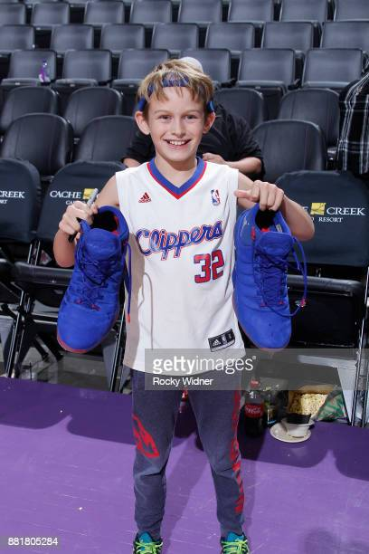 A young fan holds up the sneakers belonging to Blake Griffin of the Los Angeles Clippers after the game against the Sacramento Kings on November 25...