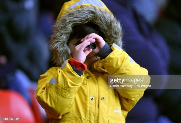 A young fan in the stands looks through a small telescope during the Premier League match at the Vitality Stadium Bournemouth