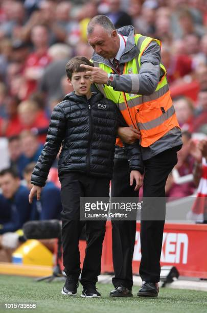 A young fan is escorted from the field by a steward after running on to hug Mohamed Salah of Liverpool during the Premier League match between...