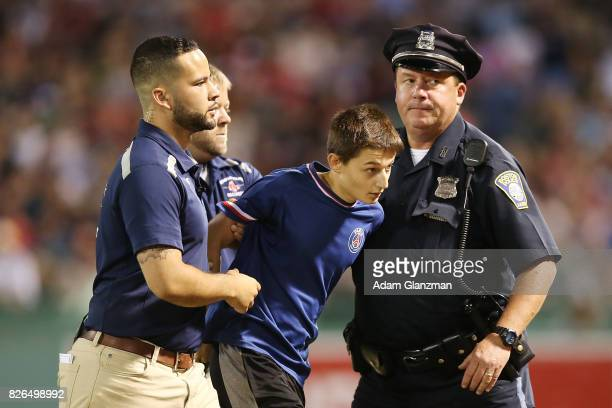 A young fan is escorted out after running on to the field during a game between the Boston Red Sox and the Chicago White Sox at Fenway Park on August...