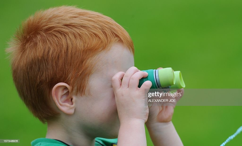 A young fan keeps is eye on the golfers during the 2012 Nedbank Golf Challenge in Sun City on December 2 ,2012.. AFP PHOTO / Alexander Joe