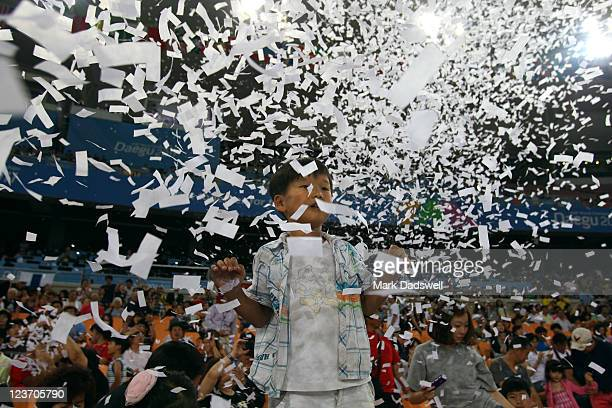 Young fan looks on as ticker tape falls during the closing ceremony during day nine of 13th IAAF World Athletics Championships at Daegu Stadium on...