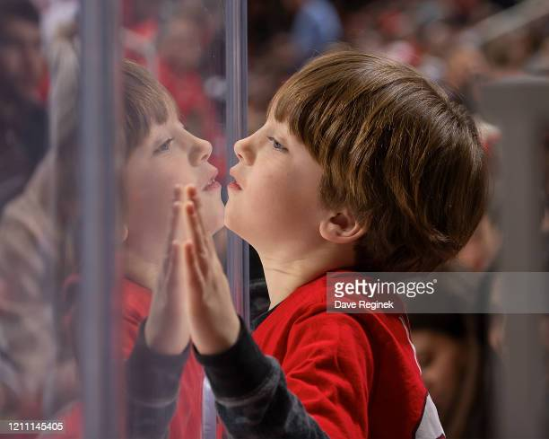 A young fan looks thru the glass during an NHL game between the Detroit Red Wings and the Chicago Blackhawks at Little Caesars Arena on March 6 2020...