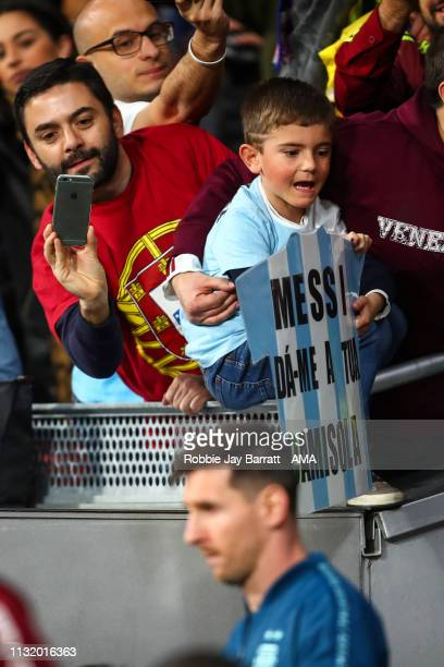 A young fan of Argentina holds up a banner for Lionel Messi or Argentina as he walks out during the International Friendly match between Argentina...