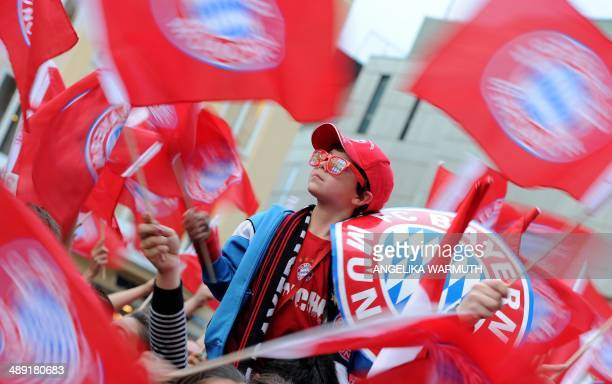 A young fan of Bayern Munich celebrates at the Marienplatz square the team's German football league champion's title after the German first division...