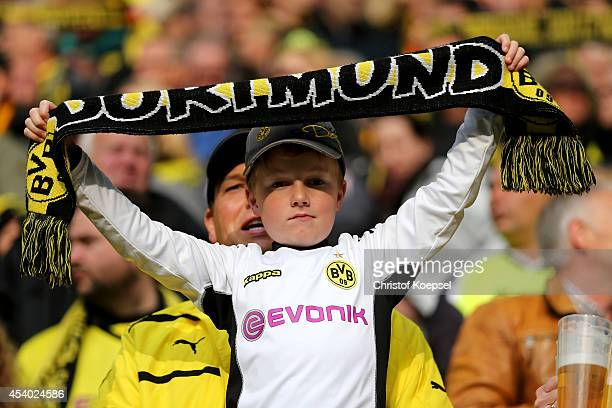 A young fan of Dortmund shows a scarf prior to the Bundesliga match between Borussia Dortmund and Bayer 04 Leverkusen at Signal Iduna Park on August...