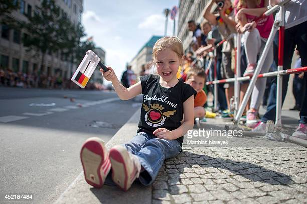 A young fan of Germany waits for the German soccer team to arrive at Brandenburg Gate to celebrate on stage at the German team victory ceremony on...