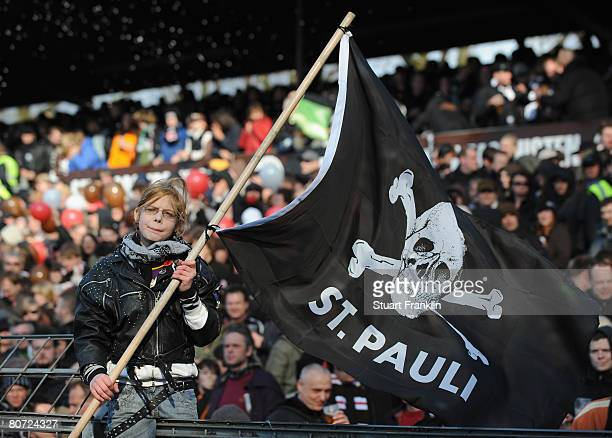 A young fan of St Pauli waves a flag during the Second Bundesliga match between FC St Pauli and 1899 Hoffenheim at the Millerntor Stadium on April 16...