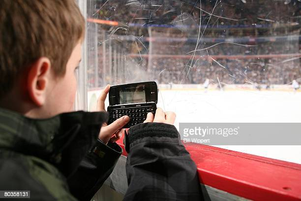 A young fan of the Buffalo Sabres sits along the glass texting on his cell phone while watching the game against the Tampa Bay Lightning on March 19...