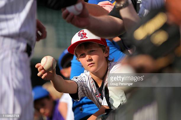 A young fan of the Colorado Rockies look to get an autograph as the Colorado Rockies host the Los Angeles Dodgers at Coors Field on June 10 2011 in...