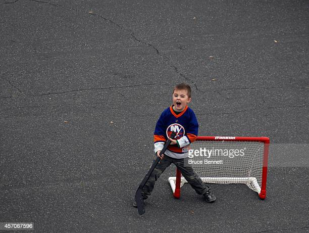 Young fan plays hockey in the parking lot prior to the game between the New York Islanders and the Carolina Hurricanes at the Nassau Veterans...