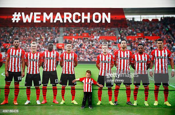 A young fan poses next to a large poster displaying Southampton players before the Barclays Premier League match between Southampton and QPR at St...