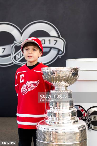 A young fan poses with the Stanley Cup during the NHL Centennial Fan Arena Truck Tour stop on Cass Avenue on December 3 2017 in Detroit Michigan