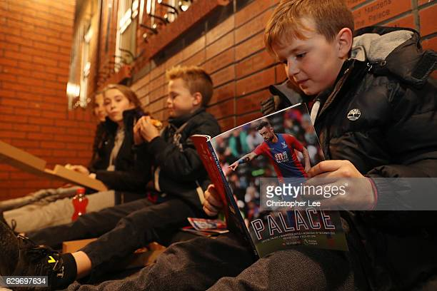 A young fan reads a match day programme prior to the Premier League match between Crystal Palace and Manchester United at Selhurst Park on December...
