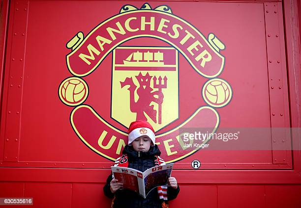 A young fan reads his matchday programme prior to kickoff during the Premier League match between Manchester United and Sunderland at Old Trafford on...