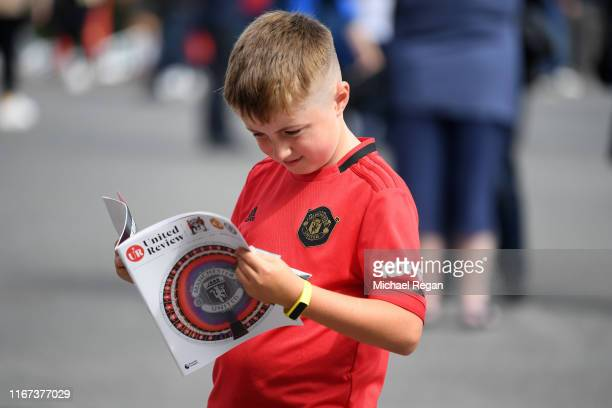 A young fan reads the match programme ahead of the Premier League match between Manchester United and Chelsea FC at Old Trafford on August 11 2019 in...