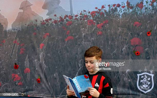 A young fan reads the matchday programme prior to the Premier League match between Huddersfield Town and West Ham United at the John Smith's Stadium...