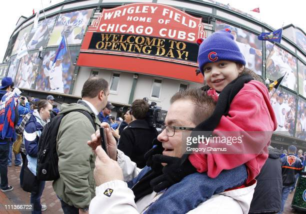 A young fan rides on her dads shoulders prior to entering the stadium for the Chicago Cubs to play the Pittsburgh Pirates during opening day at...