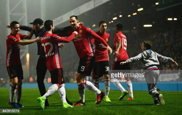 A young fan runs onto the pitch as Zlatan Ibrahimovic of Manchester United celebrates with team mates as he scores their second goal during The...