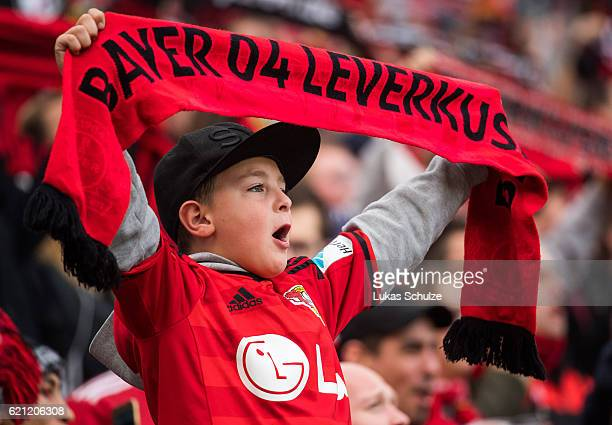 A young fan sings with a scarf of Leverkusen prior to the Bundesliga match between Bayer 04 Leverkusen and SV Darmstadt 98 at BayArena on November 5...