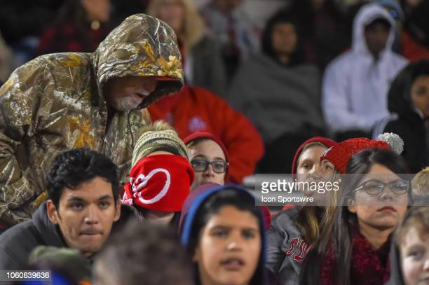 A young fan stays warm by covering his entire face with a scarf during first half action during the football game between the Temple Owls and Houston...