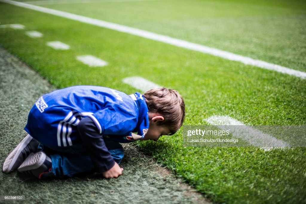 A young fan touches the gras of the pitch prior to the Bundesliga match between FC Schalke 04 and Borussia Moenchengladbach at Veltins-Arena on April 28, 2018 in Gelsenkirchen, Germany.