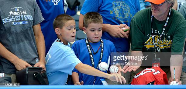 Young fan tried to get a handle on a ball as it was returned to him before the start of the All-Star Futures baseball game at Kauffman Stadium in...