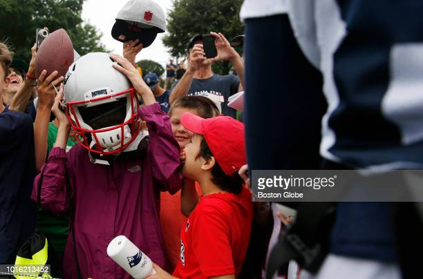 A young fan tries on Patriots wide receiver Cordarrelle Patterson's helmet after New England Patriots practice at the Gillette Stadium practice...