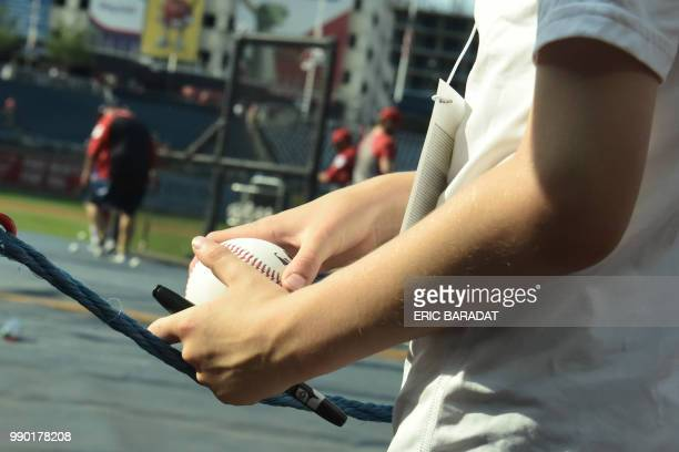 A young fan waits to get a ball signed by Washington Nationals baseball players before a game at the Nationals Park on May 21 2018 in Washington DC...