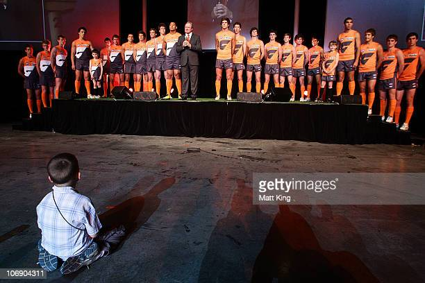 Young fan watches as Greater Western Sydney Giants head coach Kevin Sheedy speaks team players line up showing two possible new jerseys during the...
