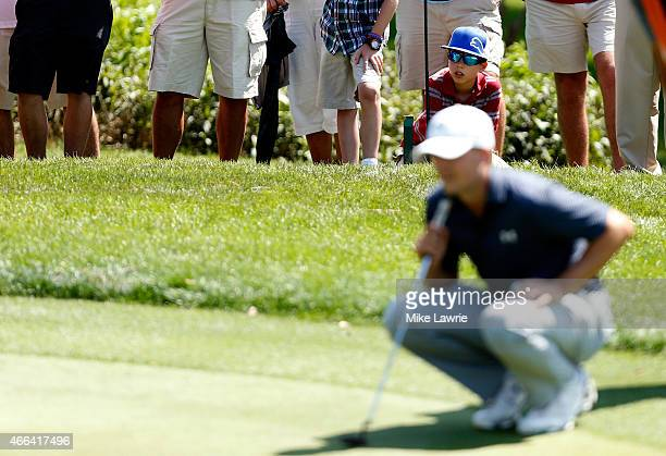 A young fan watches as Jordan Spieth lines up a putt on the first green during the final round of the Valspar Championship at Innisbrook Resort...