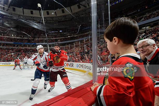 A young fan watches Brooks Laich of the Washington Capitals and Richard Panik of the Chicago Blackhawks during the NHL game at the United Center on...