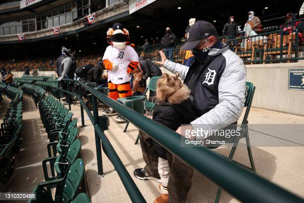 Young fan waves to the Tigers mascot Paws prior to a game between the Cleveland Indians and Detroit Tigers on Opening Day at Comerica Park on April...